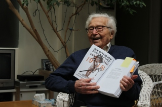John Morris will turn 100 years old this December. He has worked with such photojournalists as Robert Capa and is seen here holding what may soon be his completed memoir.