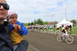 A young girl watches as racers whip around the turn and past her.